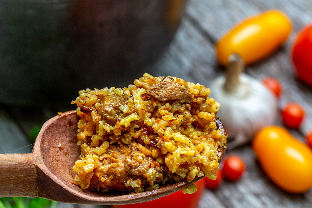 Wooden spoon with pilaf and meat close-up
