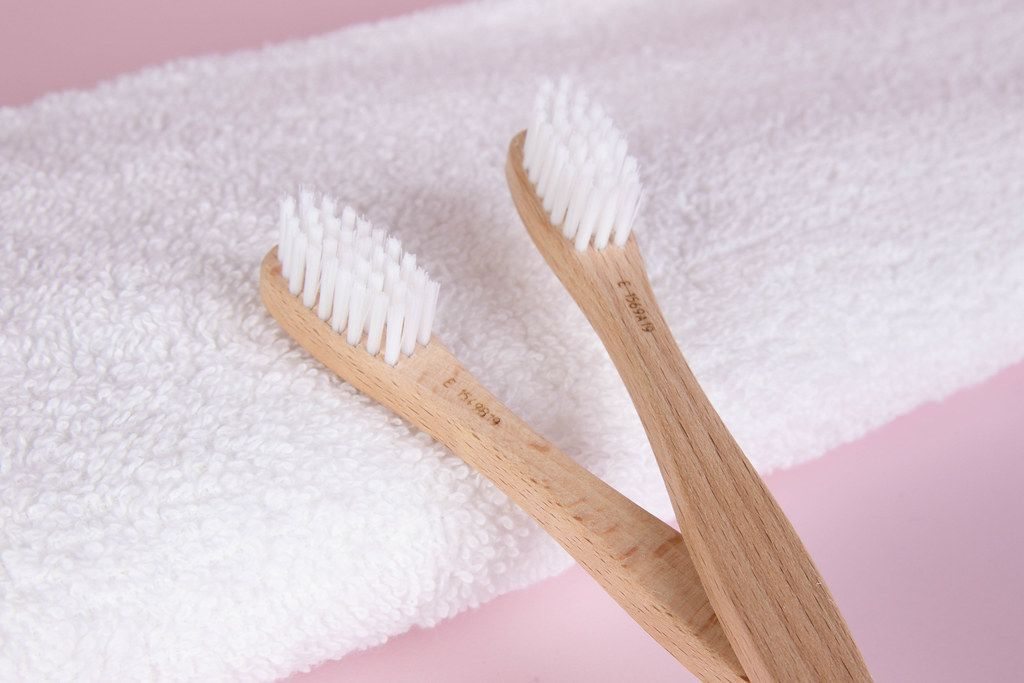 Wooden toothbrushes with towel on pink background