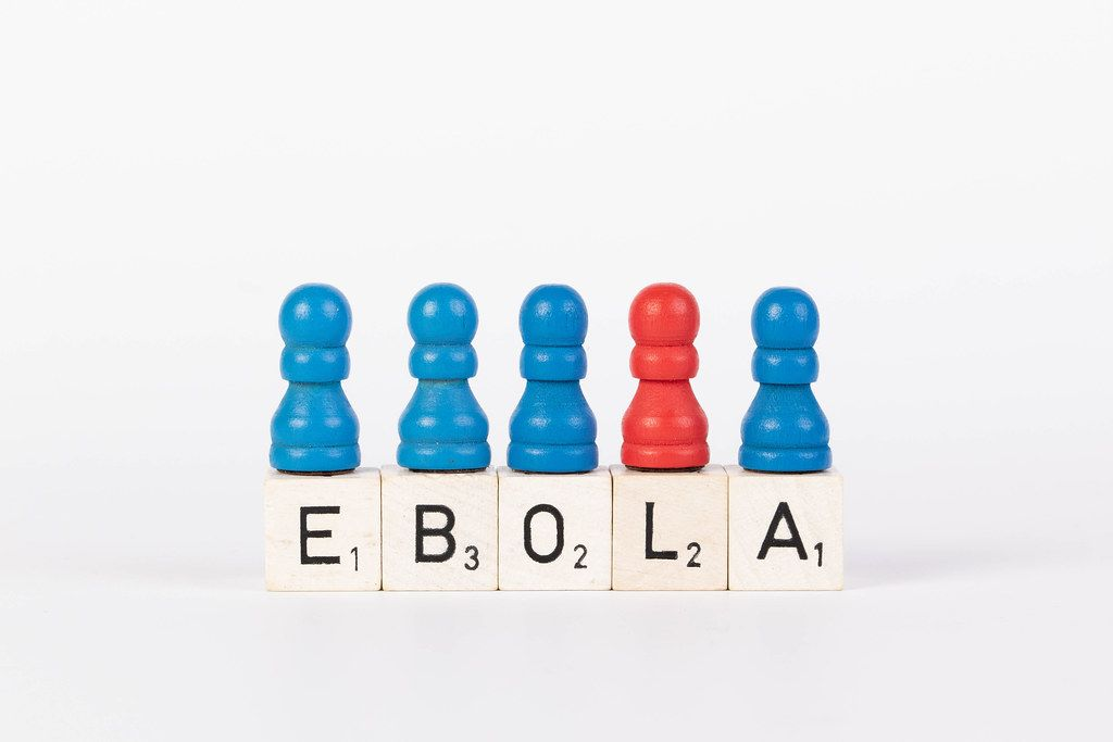 Word Ebola written on wooden blocks with pawns in various colors on white background
