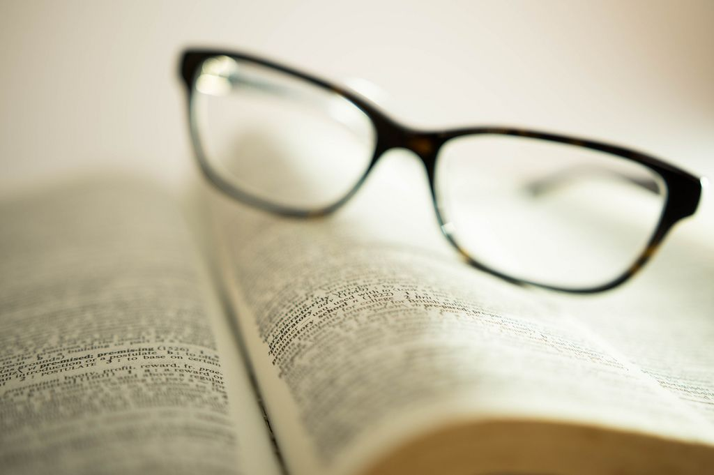 Words focused on a book with reading glasses on the background