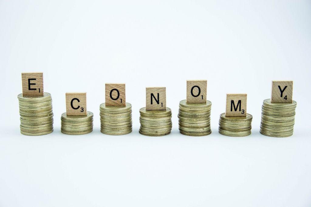 Wort ECONOMY mit Scrabble-Steinen auf Stapeln von Münzen vor weißem Hintergrund