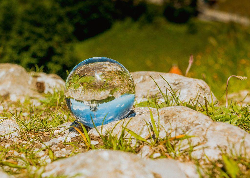 Wunderschöner, blauer Himmel spiegelt sich in der Glaskugel