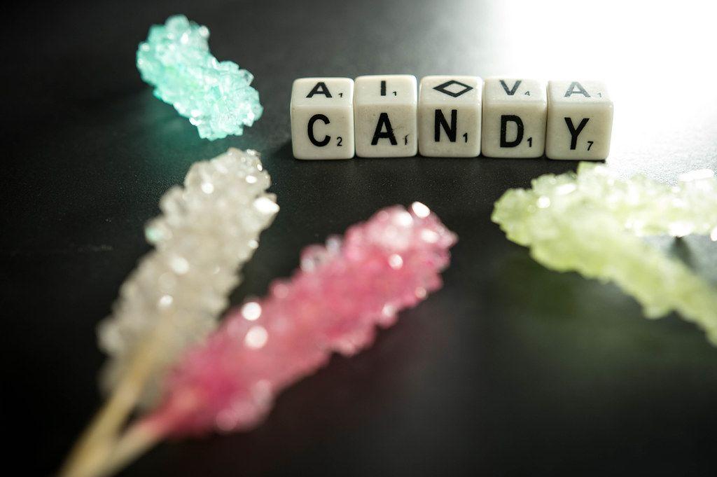 Würfel zeigen das Wort Candy - Süßigkeiten - umgeben von zuckerhaltigen Süßigkeiten in bunten Farben