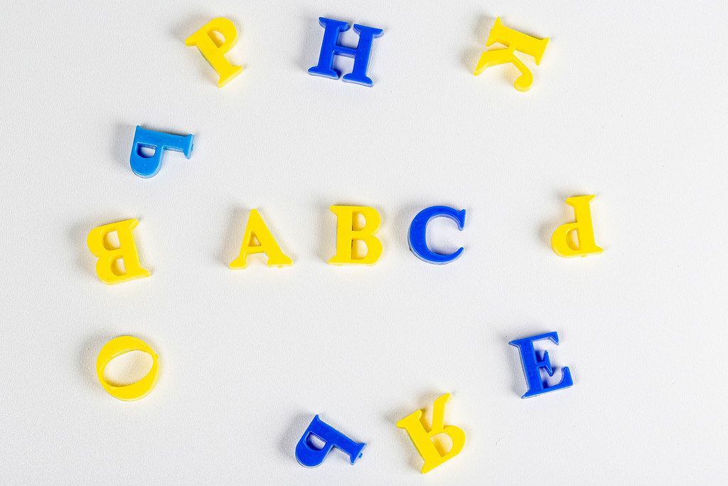 Yellow and blue plastic letters on a white background, top view