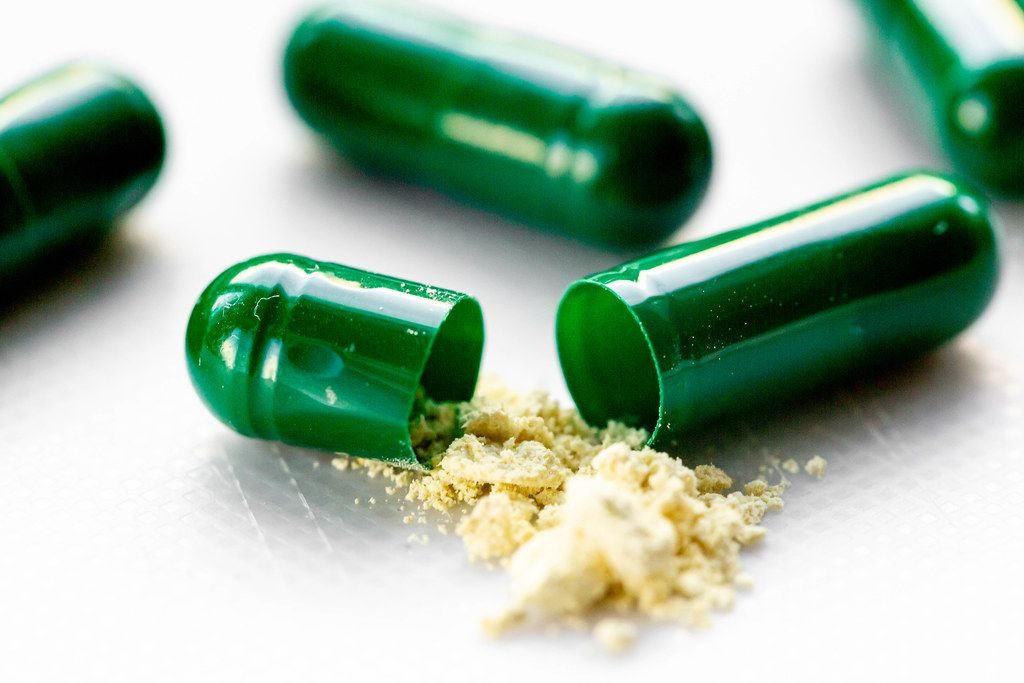 Yellow powder with green capsules. The concept of drug treatment
