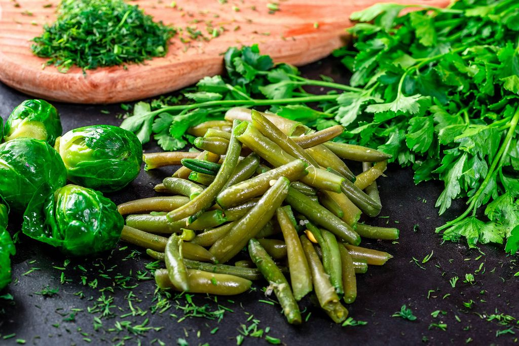 Young asparagus and Brussels sprouts on dark background with fresh parsley and dill
