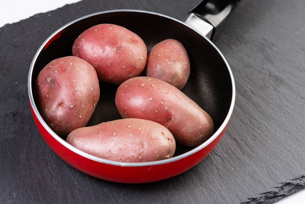 Young Potatoes in Frying Pan on the black stone tray