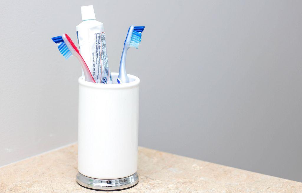 Zahnbürsten in weißer Tasse