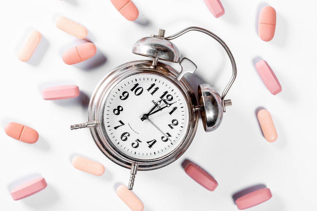 Zeit die Medikamente einzunehmen – Pillen verteilt um alten Wecker aus Metall vor weißem Hintergrund