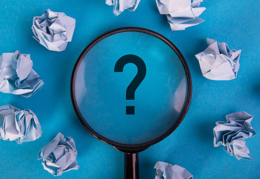 Zerknüllte Papierblätter umranden ein schwarzes Fragezeichen auf blauer Fläche, vergrößert dargestellt unter einer Lupe