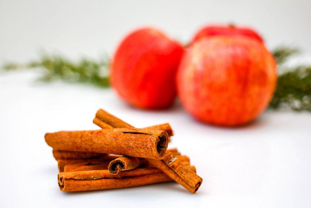 Zimtstangen und Äpfel vor weißem Hintergrund