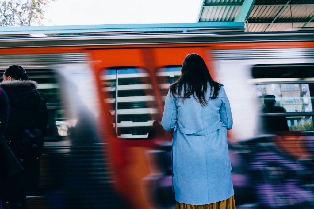 Zug fährt schnell an der Frau auf dem Bahngleis vorbei