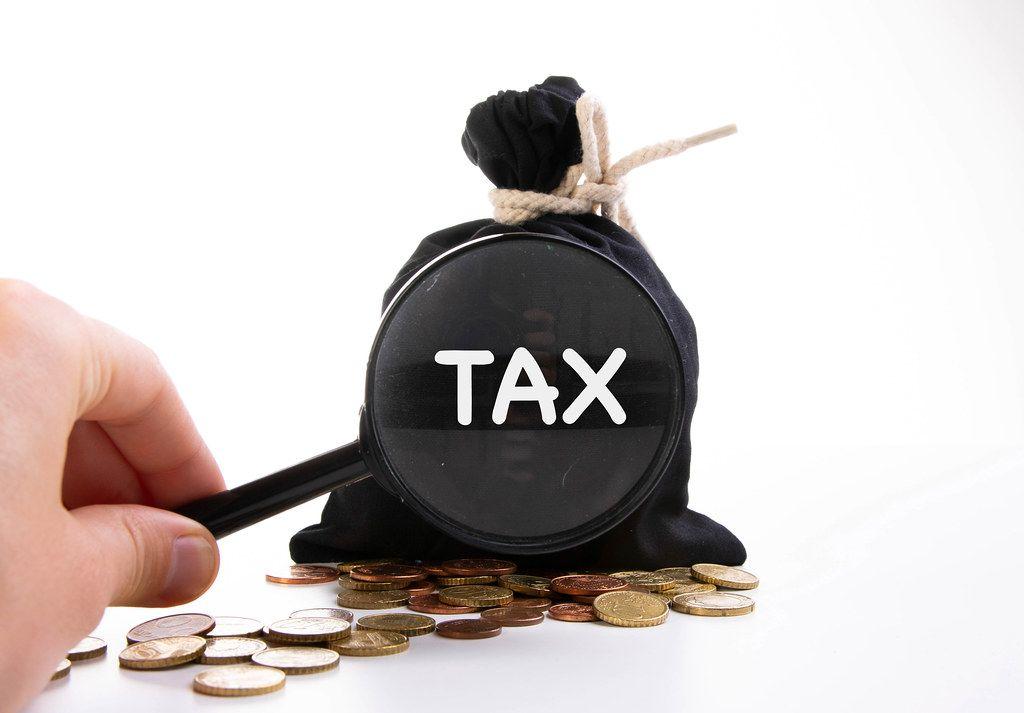 Zugeknoteter Geldsack hinter Kleingeld und der Aufschrift Steuern, vergrößert dargestellt und einer Lupe