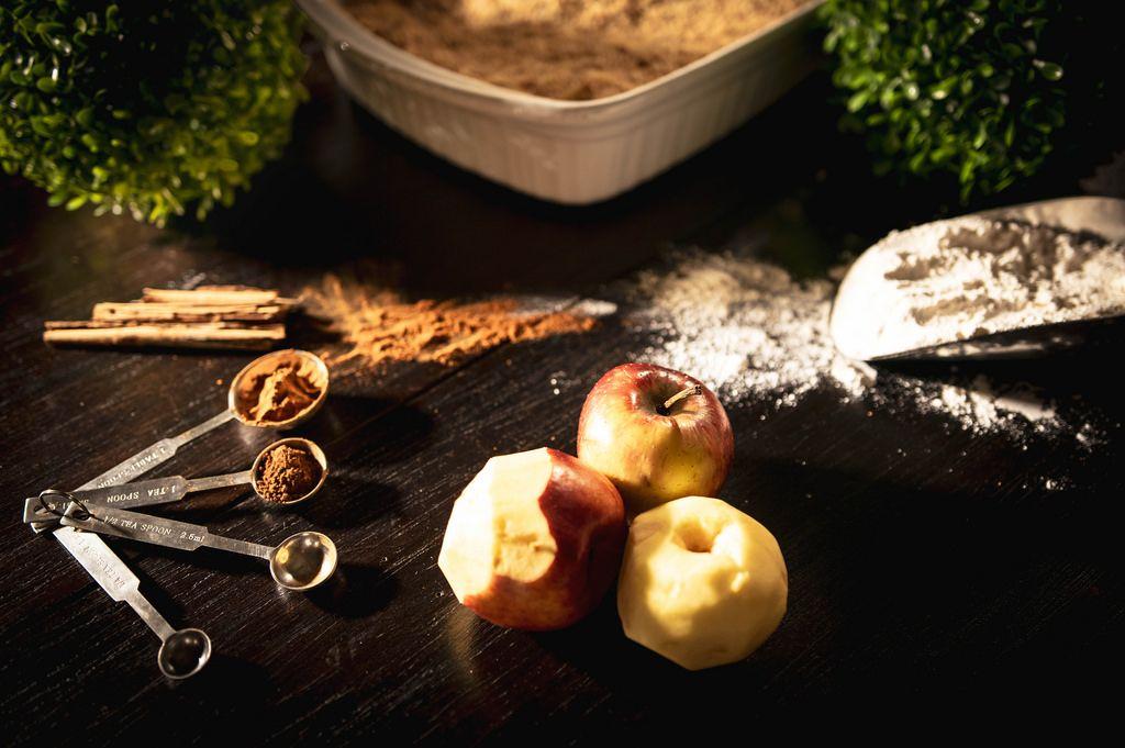 Zutaten für einen Apfel-Zimtkuchen auf schwarzem Hintergrund
