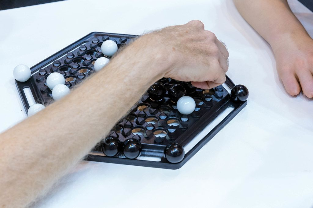 Zwei Besucher der SPIEL 19 Messe in Essen spielen Brettspiel Abalone mit sechseckigen Spielfeld und schwarzen und weißen Kugeln