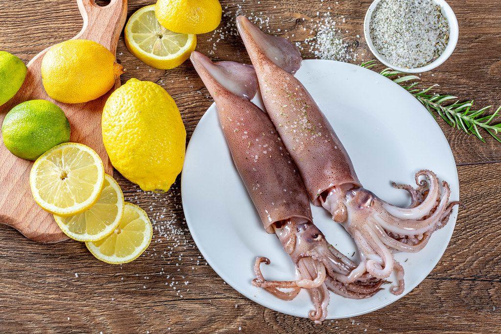 Zwei frische Tintenfische auf einem Teller, neben Zitronen und Limetten, Rosmarin und Meersalz