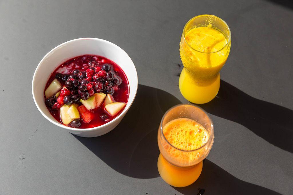 Zwei Gläser Orangensaft und ein Fruchtsalat mit Kirsche, Sauerkirsche, Apfel und Wassermelone