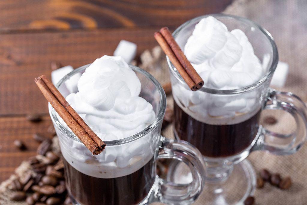 Zwei Kaffeegläser mit schwarzem Kaffee und geschlagener Sahne, verziert mit Gewürzen