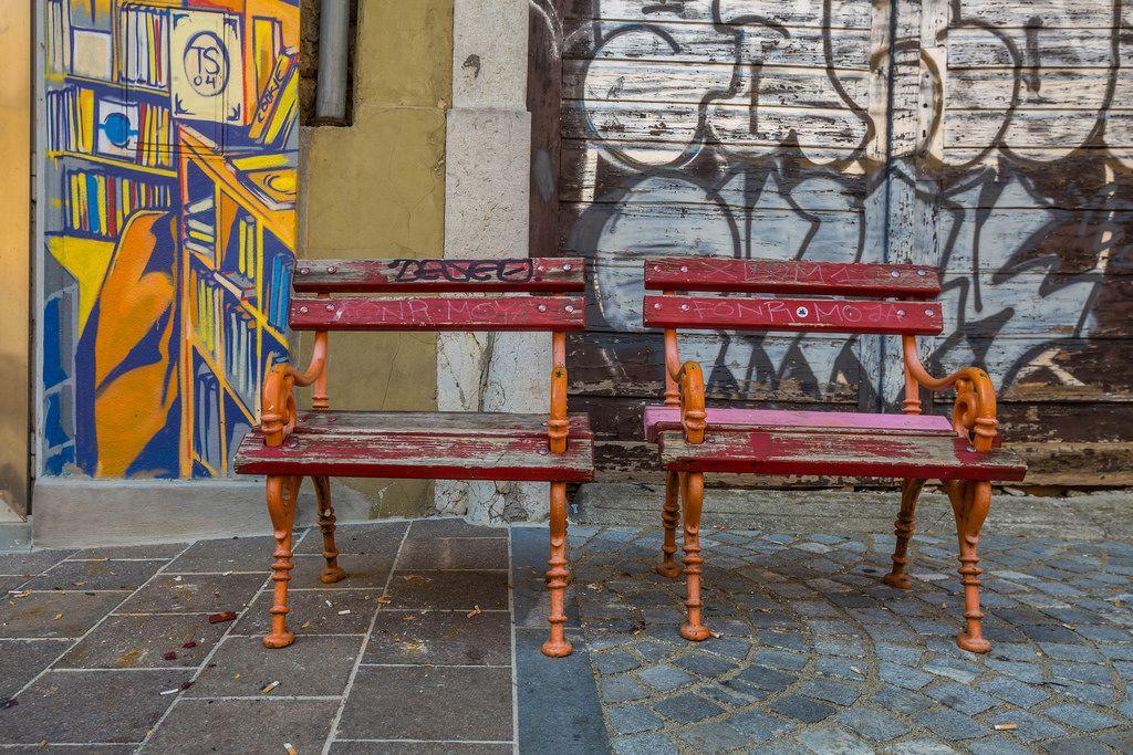 Zwei kleine rote Bänke an einer mit Graffiti bemalten Wand