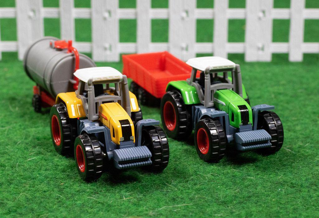 Zwei Spielzeug Traktoren auf grünem Untergrund