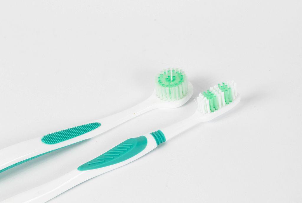 Zwei Zahnbürsten unterschiedlicher Kopfformen vor weißem Hintergrund