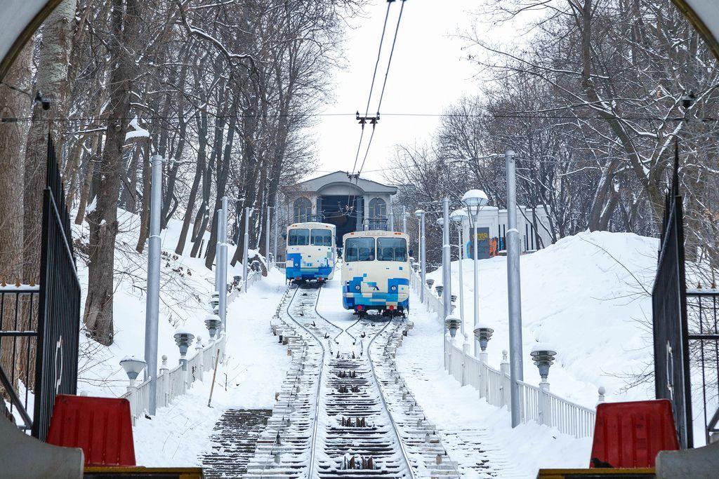 Zwei Zahnradbahnen im verschneiten Kiew mit Blick von unten auf Schienen
