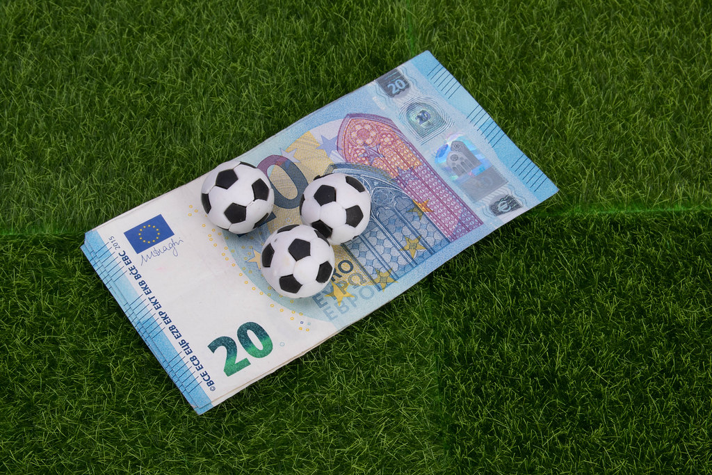 20 Euro banknote with soccer balls on green grass
