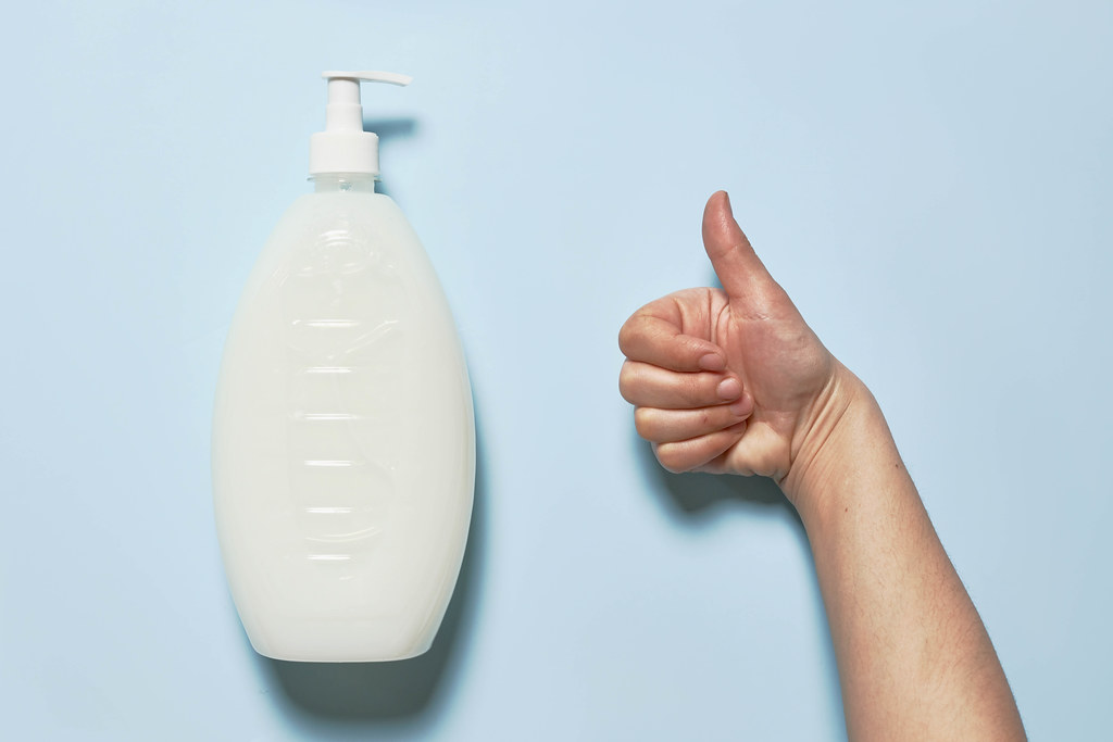 A big bottle of liquid soap and hand showing thumbs-up gesture