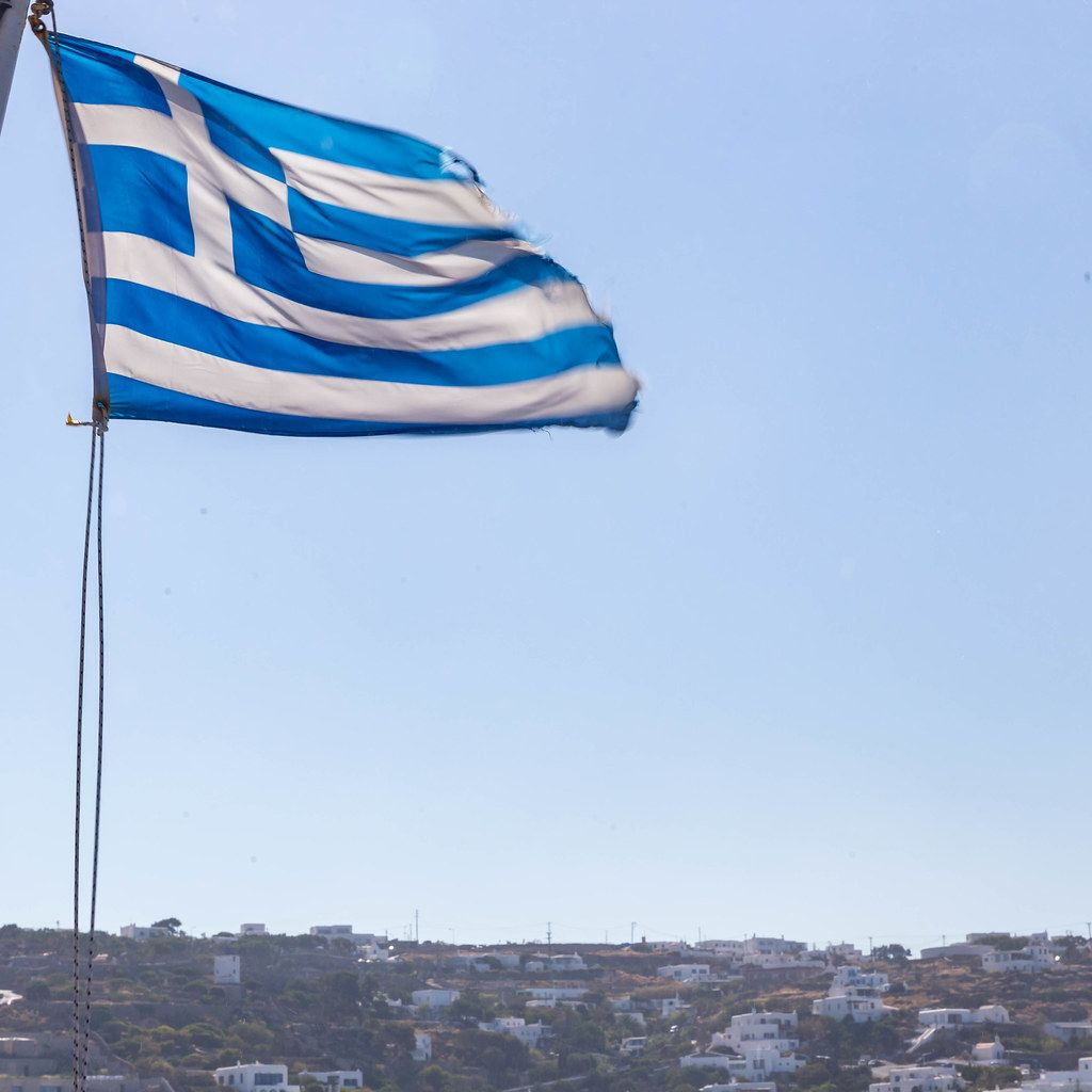 A blue and white Greek flag in the wind against the sky on the island of Mykonos