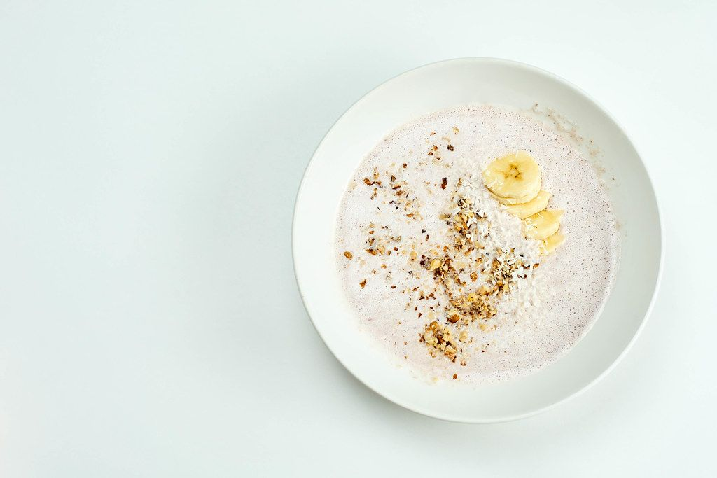 A bowl of refreshing oats and banana based smoothie with walnut shreds
