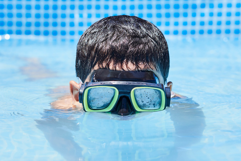 A boy in diving mask having fun in the swimming pool