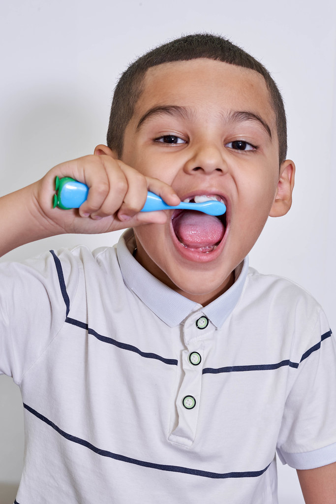 A child with funny face brushing his teeth before going to bed