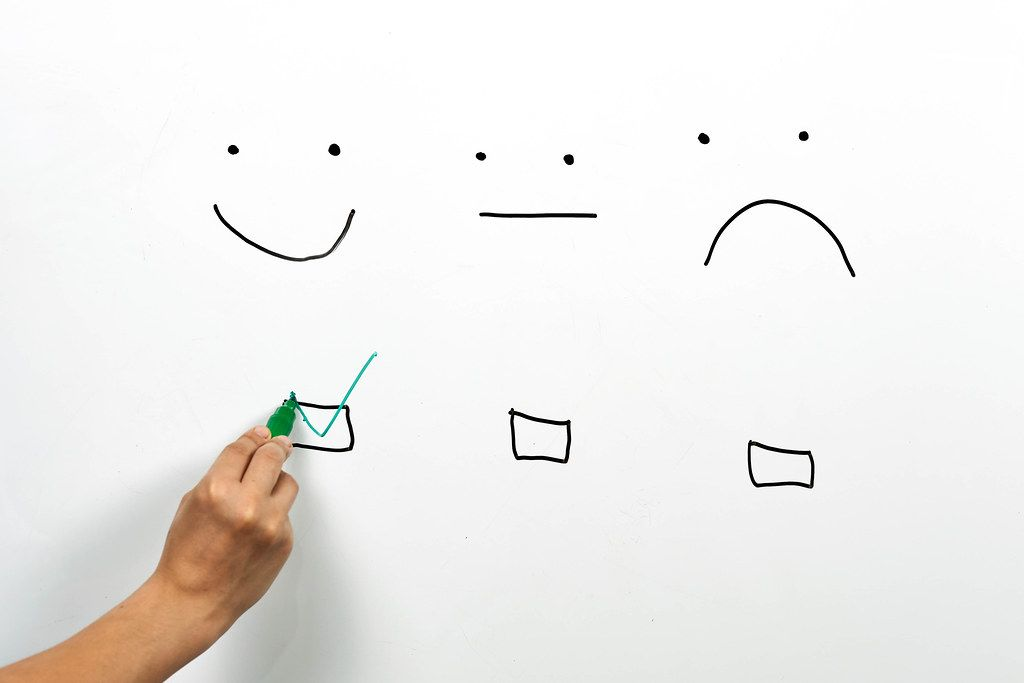 A client checking smiley face box on the whiteboard. Service rating, satisfaction, customer experience concepts