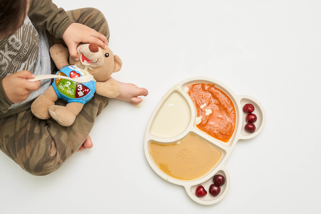 A cute little kid feeding his toy bear
