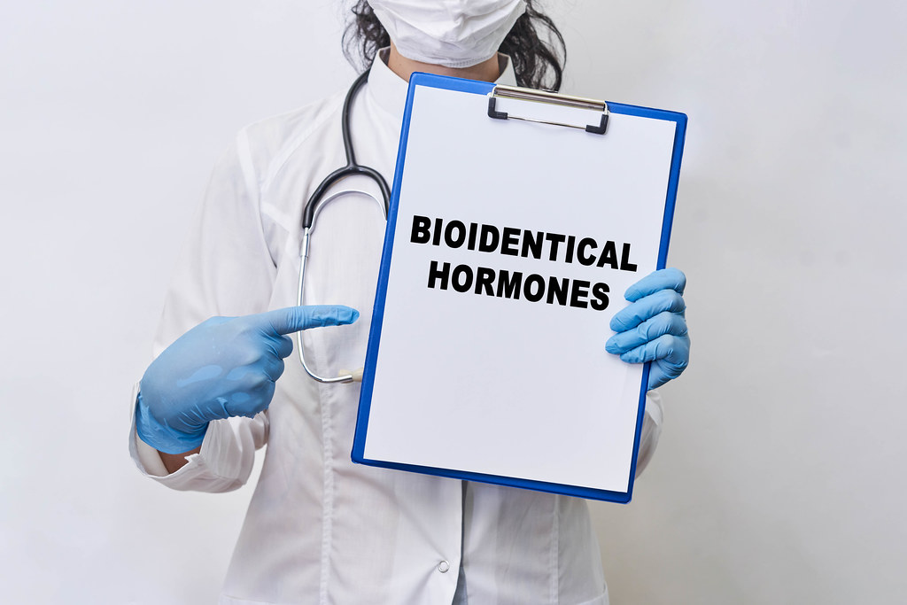 A doctor holds a paper card with text - Bioidentical hormones