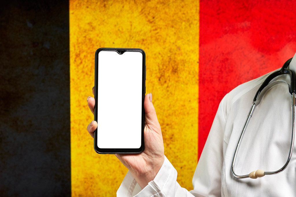 A doctor holds a smartphone with a blank screen over the Belgian flag