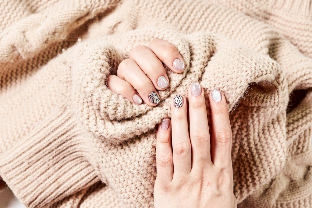 A female in a warm sweater showing her beautiful winter manicure