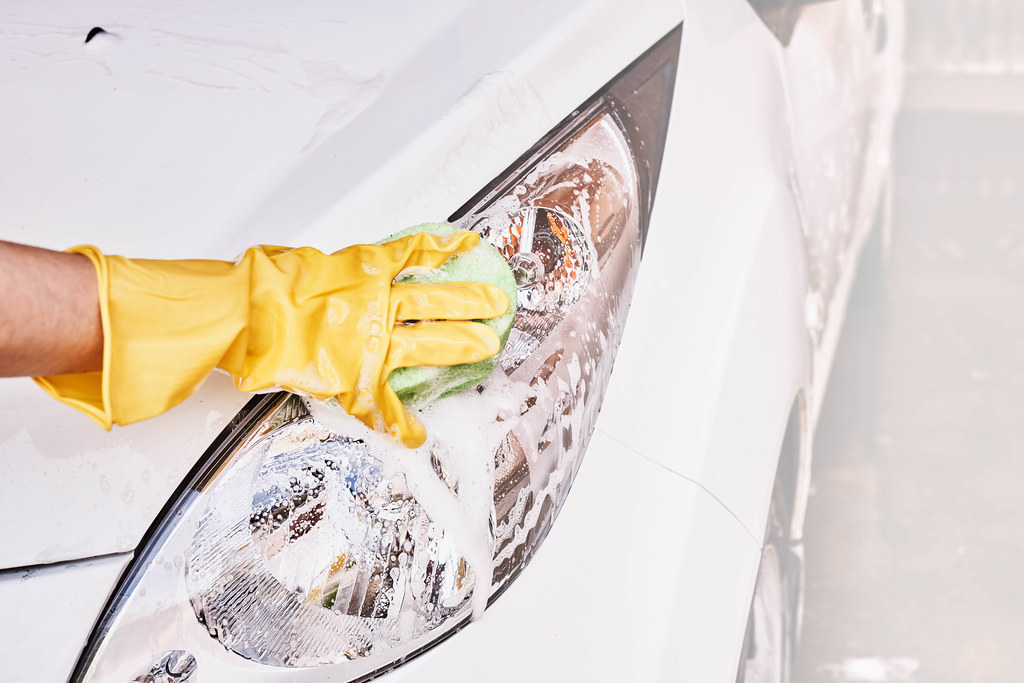 A female person in rubber gloves scrubbing vehicle front lights