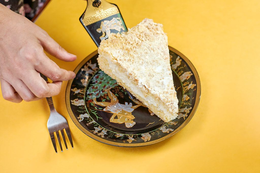 A female putting sliced piece of tasty cake on the plate