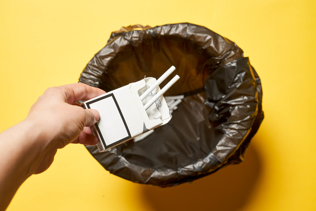 A female throwing cigarettes pocket into the garbage can - concept of quitting smoking