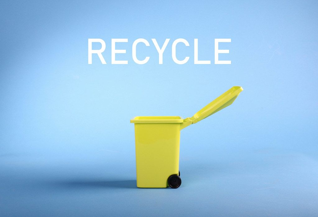 A garbage can on blue background with Recycle text