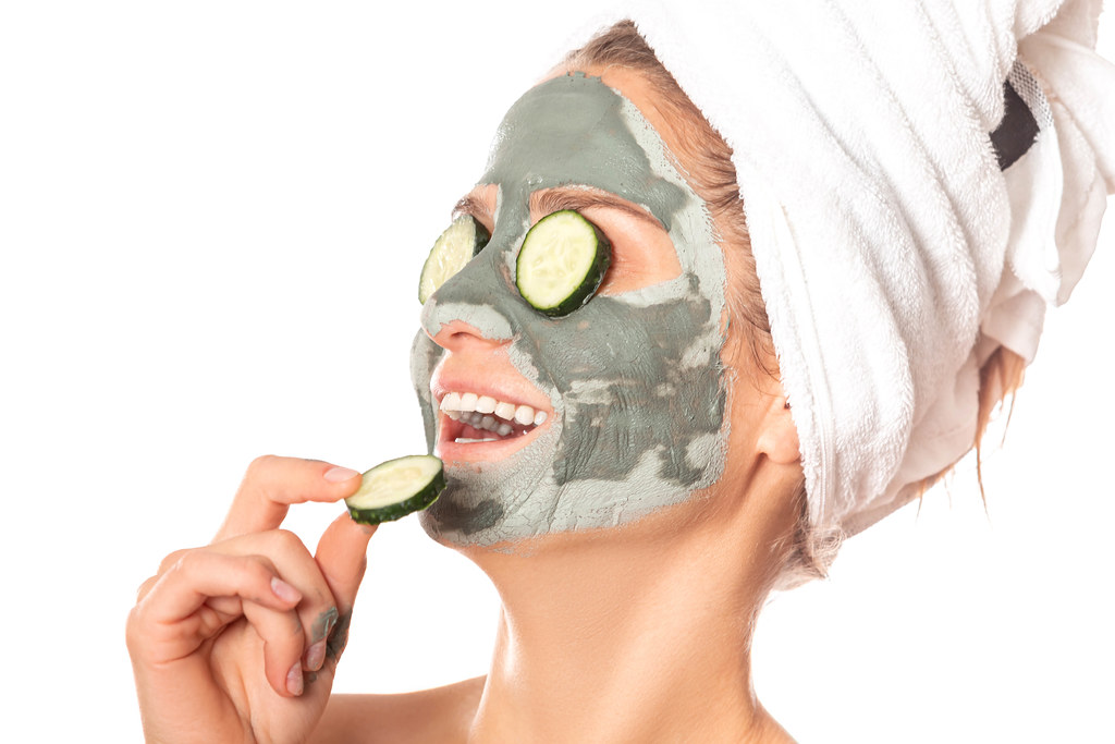 A girl with a gray clay mask on her face laughs with an open mouth and pieces of cucumbers on her eyes and in her hand