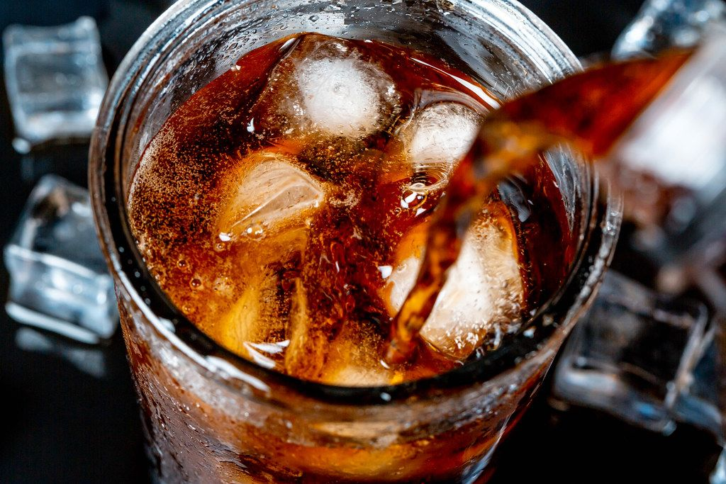 A glass of cold Pepsi with ice on a dark background