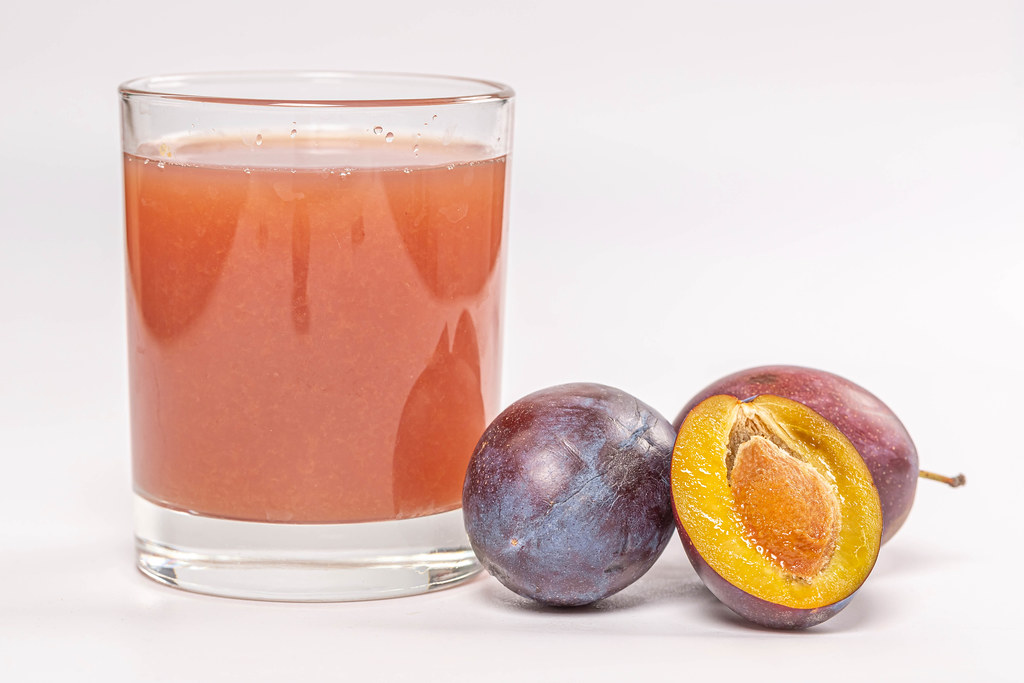 A glass of fresh plum juice with fresh ripe plums