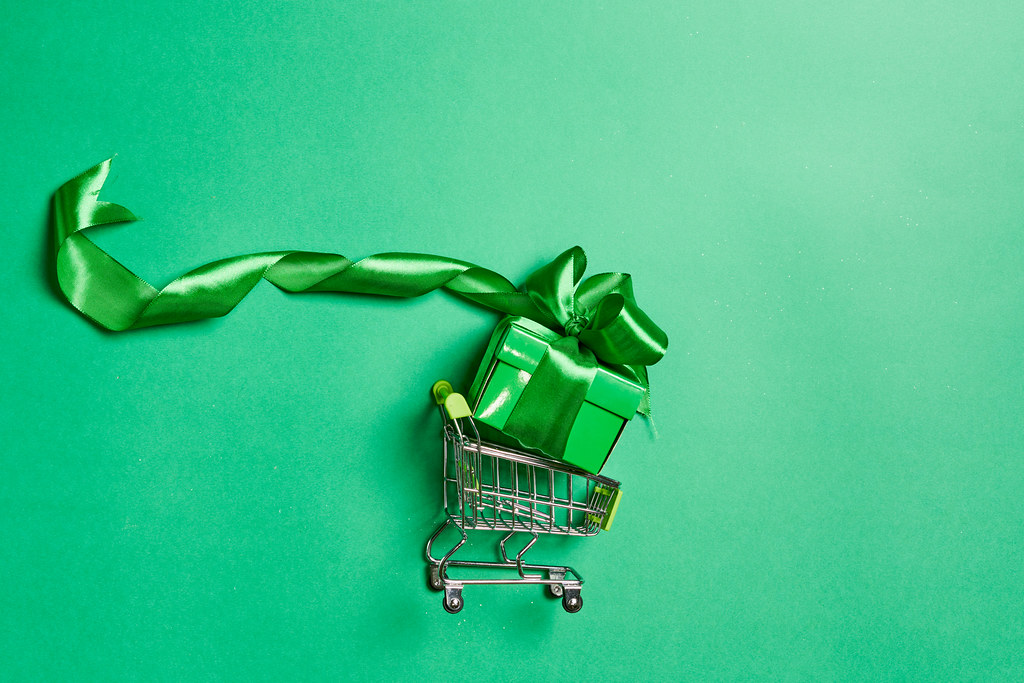 A green giftbox in the shopping cart. Top view