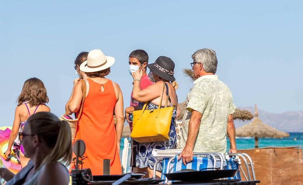 A group of tourists in Mallorca in summer 2020, some wearing a face mask against Covid-19 infection