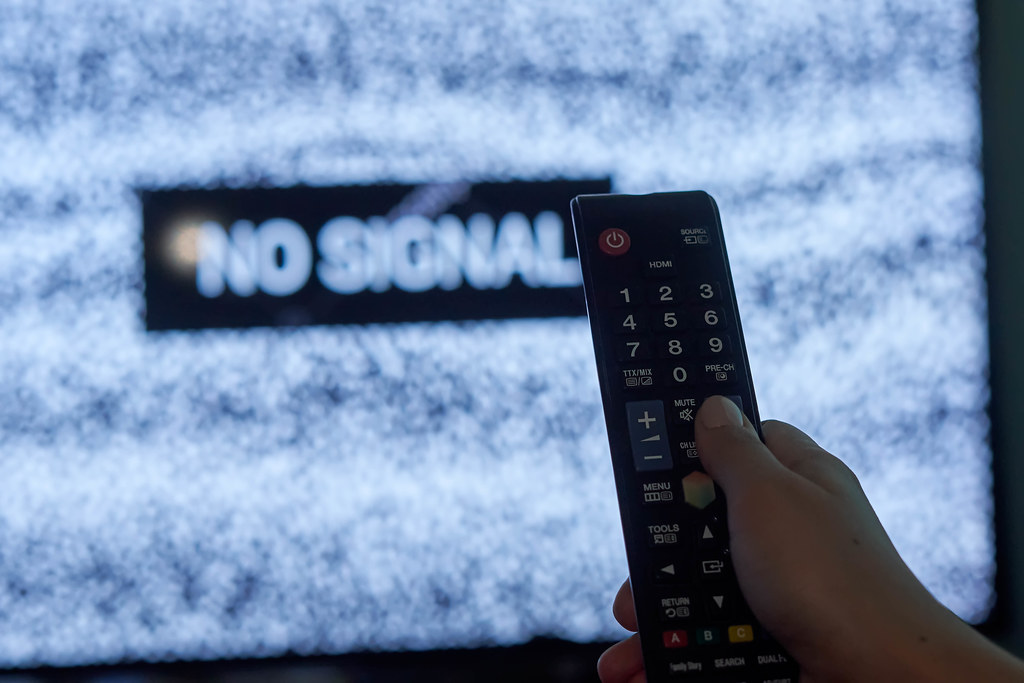 A hand holding tv remote over the TV display with