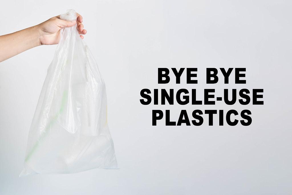 A hand holds a bag of plastics - bye-bye single-use plastics