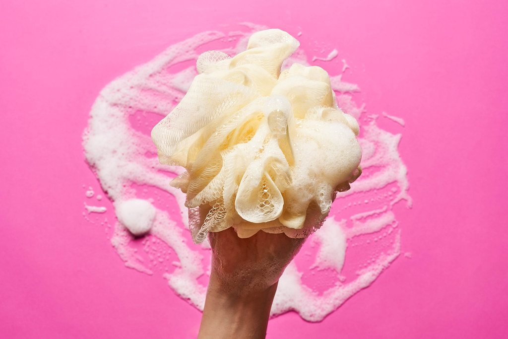 A hand of female holds skin sponge with foam over pink background