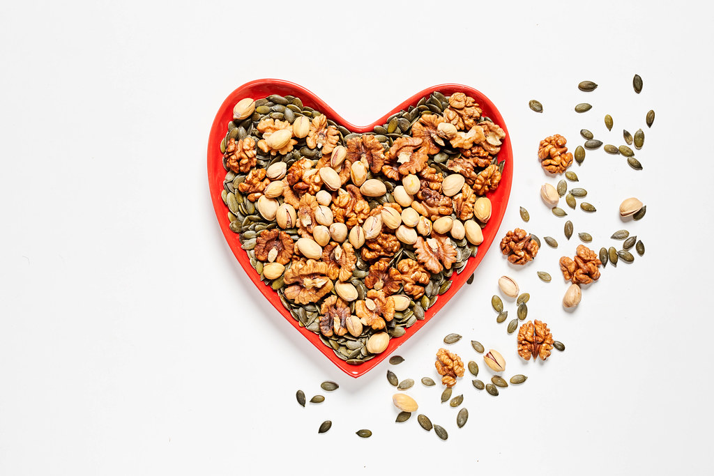 A heart-shaped plate full with various types of nuts on white backdrop